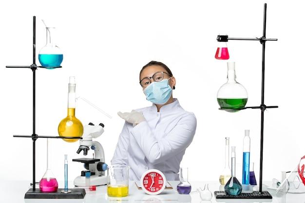 Vorderansicht weibliche chemikerin im medizinischen anzug mit maske, die mit lösungen auf weißem hintergrundspritzviruschemie-covid-labor sitzt