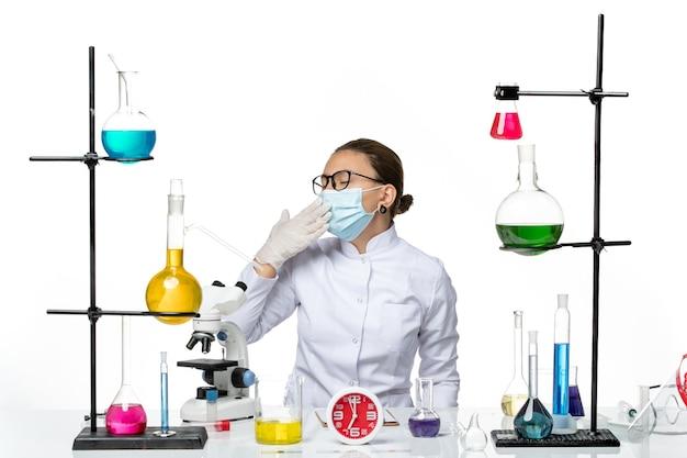 Vorderansicht weibliche chemikerin im medizinischen anzug mit maske sitzend mit lösungen, die auf weißem hintergrundviruslaborchemie-covid-spritzer gähnen