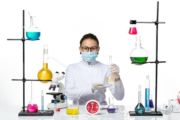Vorderansicht weibliche chemikerin im weißen medizinischen anzug mit maske vor tisch mit lösungen auf weißem hintergrund chemikerlabor virus covid splash