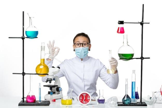 Vorderansicht weibliche chemikerin im weißen medizinischen anzug mit maskenhaltelösung auf weißem hintergrundchemikerlaborvirus-covid-spritzer