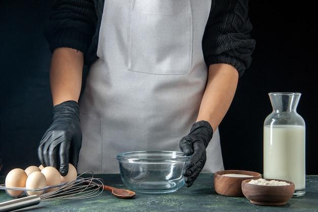 Vorderansicht weibliche köchin, die sich darauf vorbereitet, etwas mit milcheiern und mehl auf dunklem gebäck zu kochen, kuchenkuchen, bäckereiarbeiterküche?