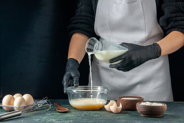 Vorderansicht weibliche köchin gießt milch in eier auf dunklem gebäck kuchen kuchen arbeiter teig küche job hotcakes