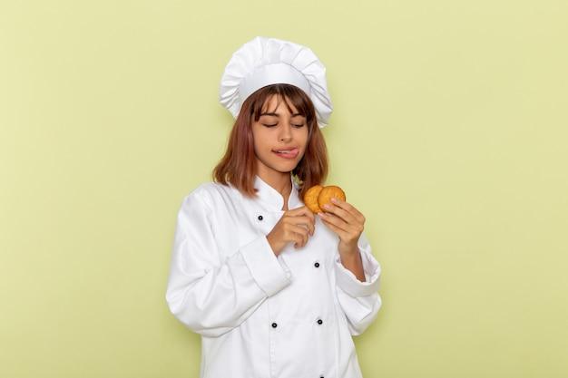 Vorderansicht weibliche köchin im weißen kochanzug, der kekse auf grüner oberfläche isst