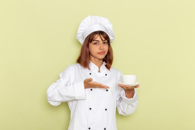 Vorderansicht weibliche köchin im weißen kochanzug, der tasse tee auf grüner oberfläche hält