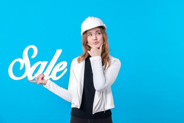 Vorderansicht weiblicher architekt, der verkaufsschreiben auf blauem arbeiter-konstruktor-architektur-wohnungsbauer-jobhaus hält