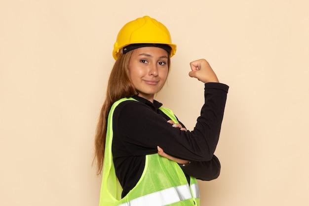 Vorderansicht weiblicher baumeister im gelben helm, der auf weißem wandweibchen lächelt und sich biegt