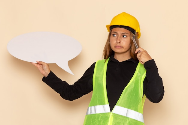 Vorderansicht weiblicher baumeister im gelben helm, der ein großes weißes zeichen silbernes werkzeug hält, das auf weiße schreibtischfrau denkt