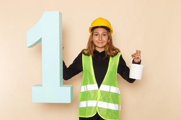 Vorderansicht weiblicher baumeister im gelben helm, der farbe und nummer eins figur auf weißer wand hält