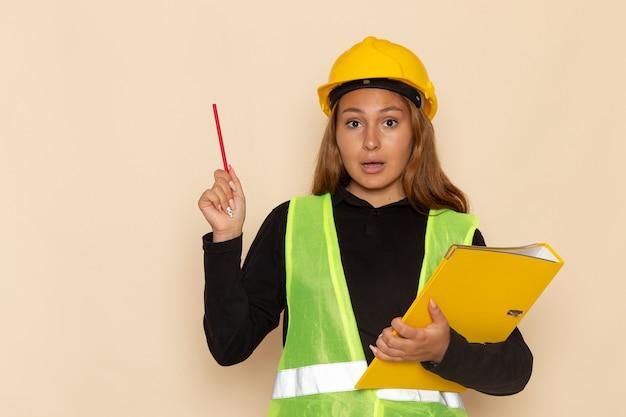 Vorderansicht weiblicher baumeister im gelben helm, der gelbe datei und bleistift auf weißer wand hält