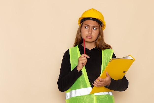 Vorderansicht weiblicher baumeister im gelben helm, der gelbe datei und bleistift denkt auf weißer wand hält