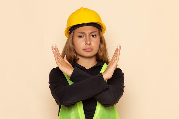 Vorderansicht weiblicher baumeister im gelben helm, der mit unzufriedenem ausdruck auf weißem wandweibchen aufwirft