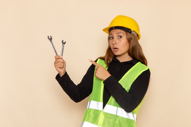 Vorderansicht weiblicher baumeister im gelben helm, der silberne instrumente auf der lichtwand weiblicher architekt hält