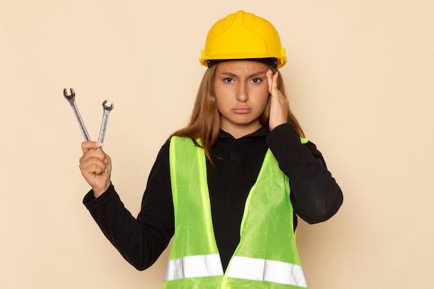 Vorderansicht weiblicher baumeister im gelben helm, der silberne instrumente hält, die kopfschmerzen auf weiblichem architekten des hellen schreibtisches haben