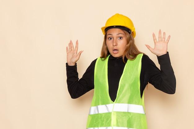 Vorderansicht weiblicher baumeister im gelben helmschwarzhemd, das mit erhabenen händen auf dem weißen schreibtisch weiblicher baumeisterbaufrau aufwirft
