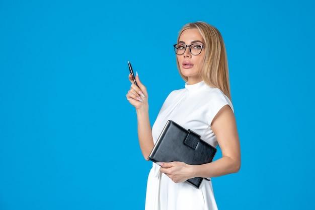 Vorderansicht weiblicher in weißem kleid posiert mit notizblock auf blauer arbeitsbehörde