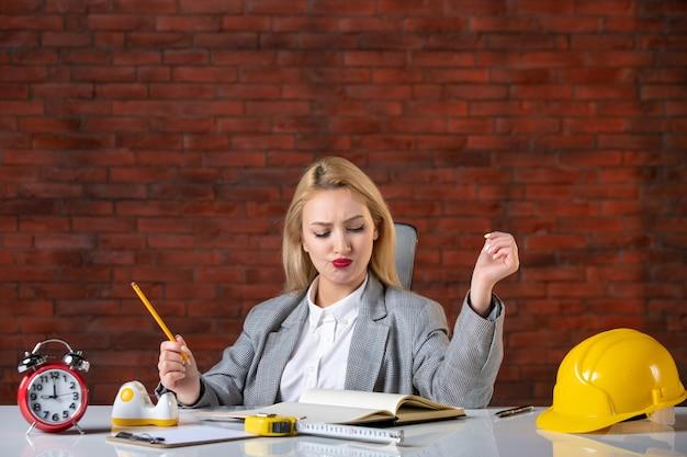 Vorderansicht weiblicher ingenieur, der hinter ihrem arbeitsplatz sitzt