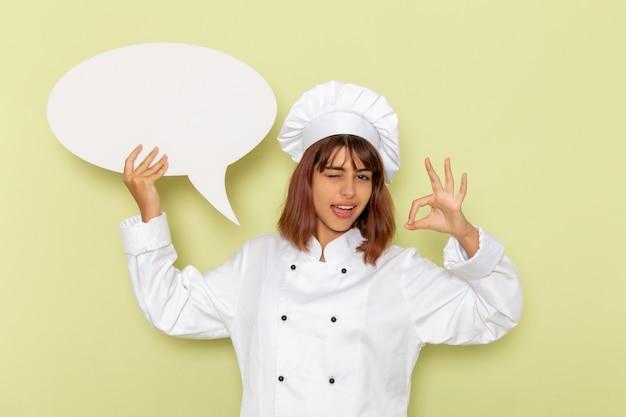 Vorderansicht weiblicher koch im weißen kochanzug, der ein großes weißes zeichen auf grünem schreibtisch hält