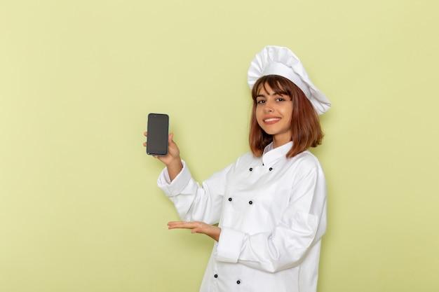 Vorderansicht weiblicher koch im weißen kochanzug, der ihr smartphone auf grüner oberfläche hält