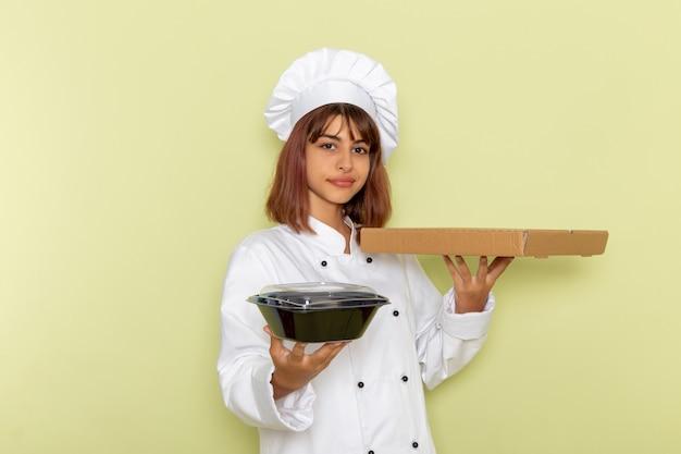 Vorderansicht weiblicher koch im weißen kochanzug, der nahrungsmittelbox und schwarze schüssel auf grüner oberfläche hält