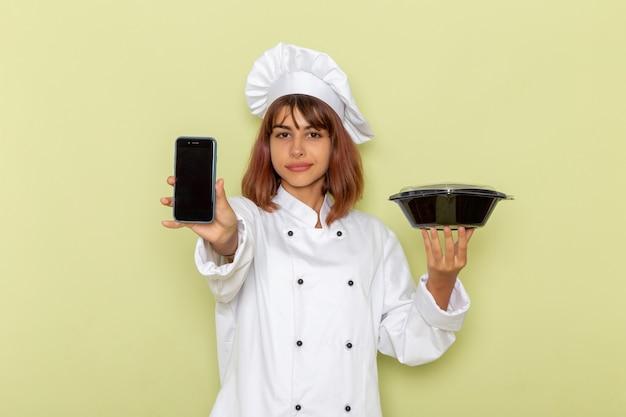 Vorderansicht weiblicher koch im weißen kochanzug, der telefon und schwarze schüssel auf grüner oberfläche hält
