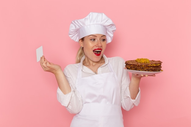 Vorderansicht weiblicher konditor in der weißen abnutzung, die köstliches gebäck und weiße karte auf der rosa wandkonfekt süßes gebäckjobarbeit hält