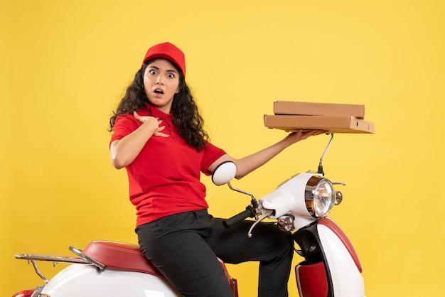 Vorderansicht weiblicher kurier auf fahrrad mit pizzakartons auf gelbem schreibtisch arbeiter service uniform job frau lieferung arbeit