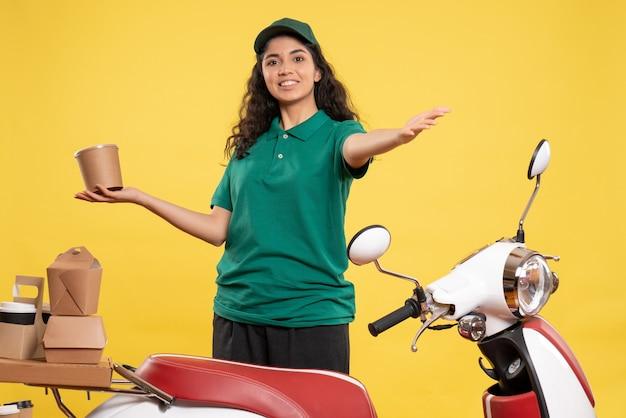 Vorderansicht weiblicher kurier in grüner uniform mit dessert auf gelbem hintergrund farbe arbeit job lieferung frau service arbeiter essen lächeln