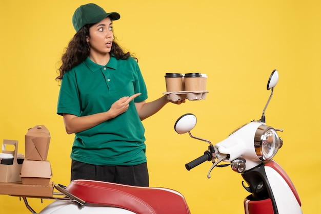 Vorderansicht weiblicher kurier in grüner uniform mit kaffee auf gelbem hintergrund farbe service arbeiter job arbeit essen frau