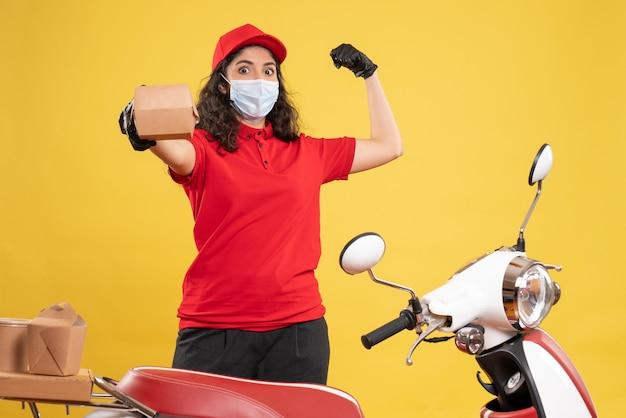 Vorderansicht weiblicher kurier in roter uniform, der ein kleines lebensmittelpaket auf gelbem hintergrund hält covid-job service delivery uniform worker pandemie