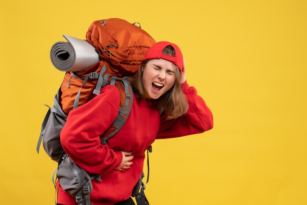 Vorderansicht weiblicher reisender mit rucksack, der magen mit schmerz hält