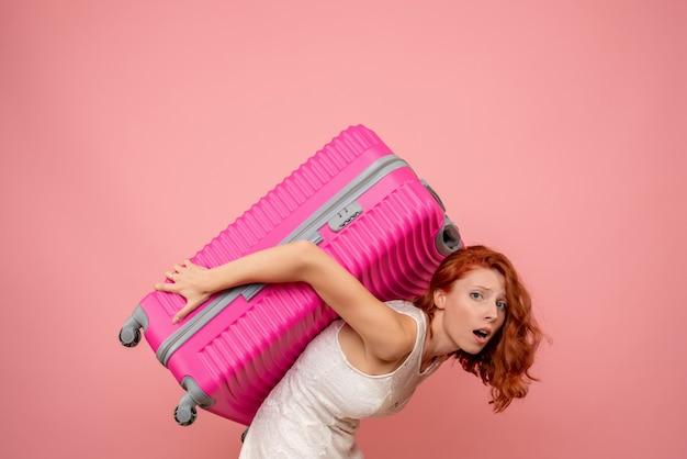 Vorderansicht weiblicher tourist, der ihre rosa tasche trägt