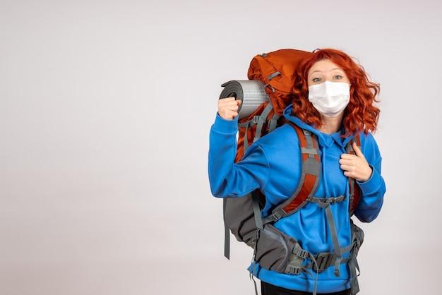 Vorderansicht weiblicher tourist, der in bergtour mit rucksack geht