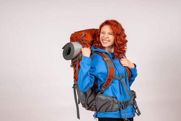 Vorderansicht weiblicher tourist, der in bergtour mit rucksackfreude geht
