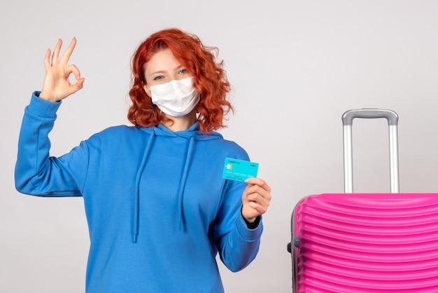 Vorderansicht weiblicher tourist in der maske, die bankkarte hält
