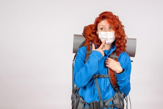 Vorderansicht weiblicher tourist in der maske mit ihrem rucksack