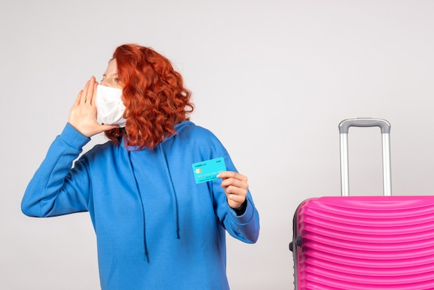 Vorderansicht weiblicher tourist in maske, die bankkarte hält und anruft