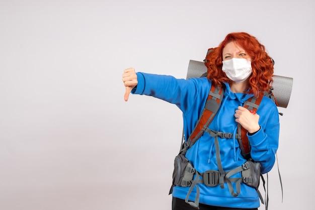 Vorderansicht weiblicher tourist in maske mit rucksack