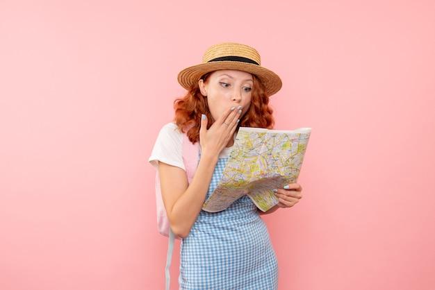 Vorderansicht weiblicher tourist mit karte, die versucht, richtung in fremder stadt zu finden