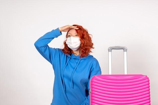 Vorderansicht weiblicher tourist mit rosa tasche in der maske