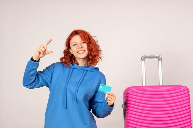 Vorderansicht weiblicher tourist mit rosa tasche und haltebankkarte
