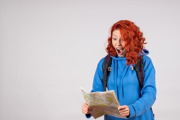 Vorderansicht weiblicher tourist mit rucksack und karte