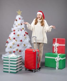 Vorderansicht-weihnachtsfrau, die beide hände nahe weihnachtsbaum offen hält