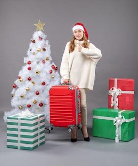 Vorderansicht-weihnachtsfrau mit weihnachtsmütze, die ihre rote reisetasche hält, die daumen hoch zeichen zeigt