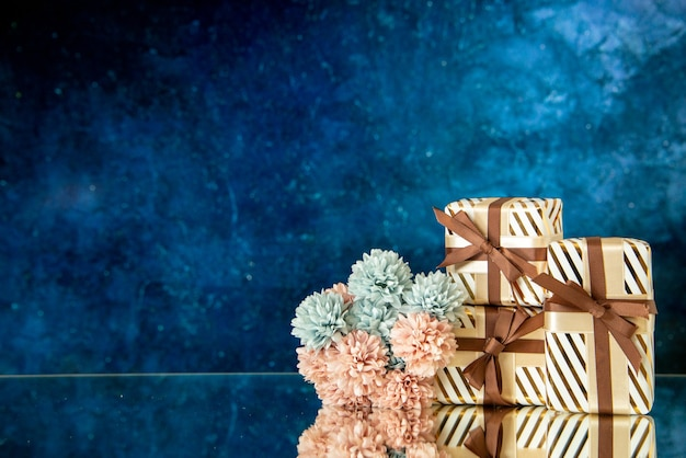 Vorderansicht weihnachtsgeschenke blumen reflektiert auf spiegel auf dunkelblauem hintergrund mit kopie platz