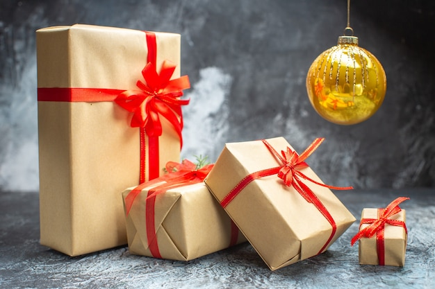 Vorderansicht weihnachtsgeschenke gebunden mit roten schleifen auf dem hell-dunklen farbfoto neujahrsfeier weihnachtsgeschenk