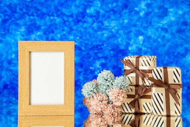 Vorderansicht weihnachtsgeschenke leere rahmenblumen reflektiert auf spiegel auf blauem hintergrund