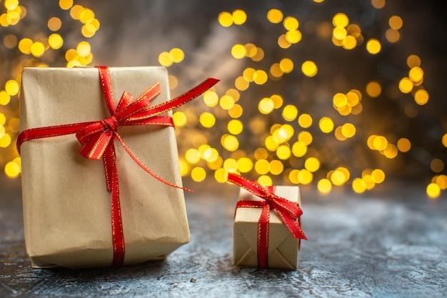 Vorderansicht weihnachtsgeschenke mit gelben lichtern auf hell-dunkler weihnachts-neujahrsfarbe