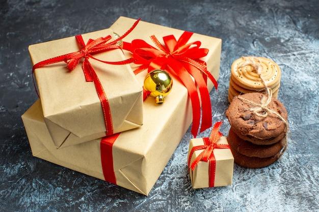 Vorderansicht weihnachtsgeschenke mit keksen auf hell-dunkel urlaub foto geschenk weihnachtsfarbe neujahr