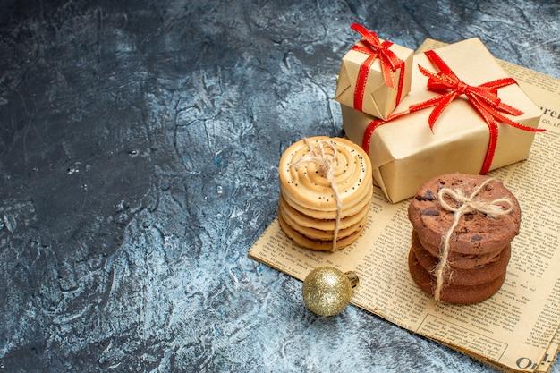 Vorderansicht weihnachtsgeschenke mit keksen und spielzeug auf hell-dunkel-geschenkfarbfoto neujahr weihnachten urlaub freiraum