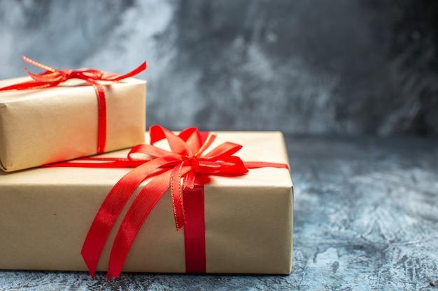 Vorderansicht weihnachtsgeschenke mit roten schleifen auf dem hell-dunklen neujahrsfoto urlaub farbe geschenk weihnachten gebunden